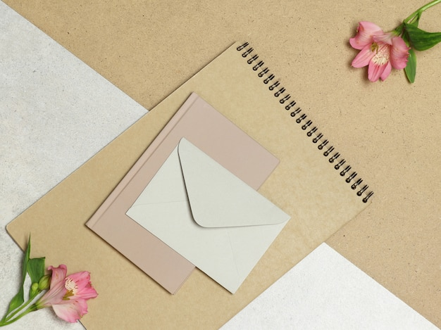 クラフトアルバム、メモ、石と木のテーブルにピンクの花の封筒