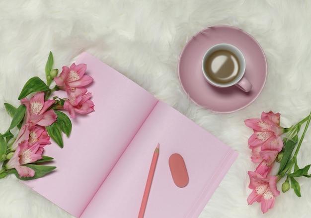 花と一杯のコーヒーで白い毛皮のような背景にピンクのメモ用紙