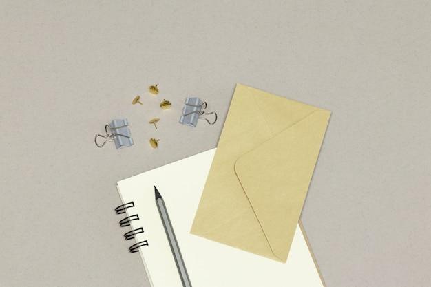 ノートブック、封筒、銀色の鉛筆&灰色の背景上のペーパークリップ
