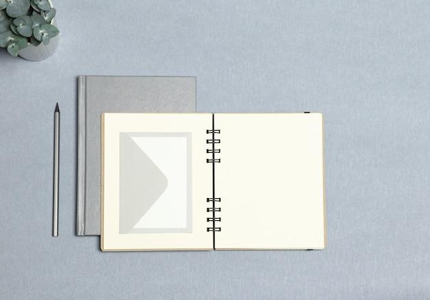 銀のノート、開いているノート、白い封筒、銀色の鉛筆、灰色の背景に緑の植物