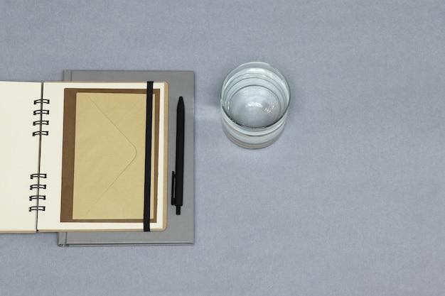 灰色のノートブック、黒いペン、封筒、紙の背景に水の入ったグラス