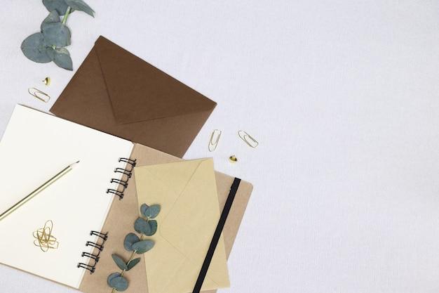 手紙を書く。開いたノート、封筒、金色の鉛筆、ペーパークリップ、ピン、ユーカリの枝