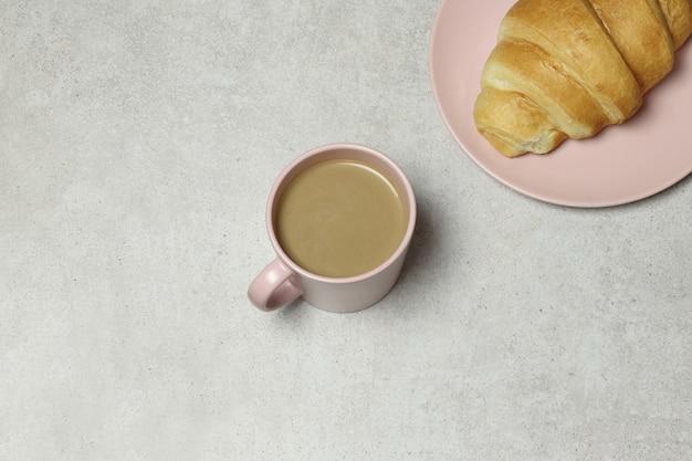 ピンクのコーヒーカップと花崗岩の背景にクロワッサン