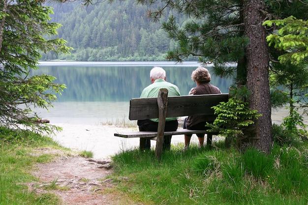 Пожилая пара сидит на скамейке у озера
