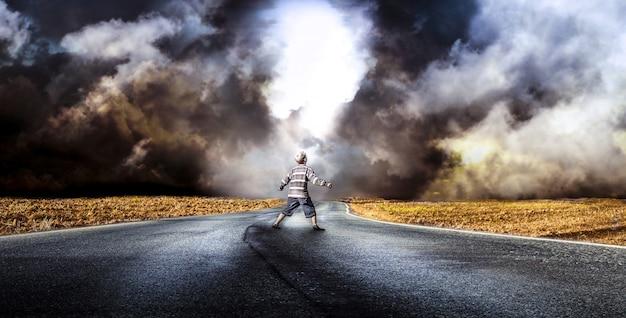 嵐を待っている道路の真ん中に小さな男の子
