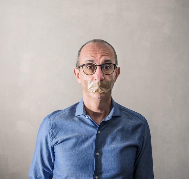 口にダクトテープを持つ男