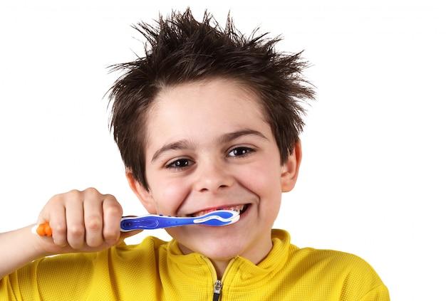 少年は彼の歯を磨いています。