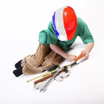 Молодой французский мальчик, играя с инструментами для работы