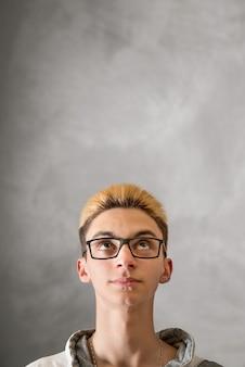灰色の背景で見上げる少年