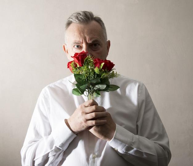 彼の手に花の束を持って男