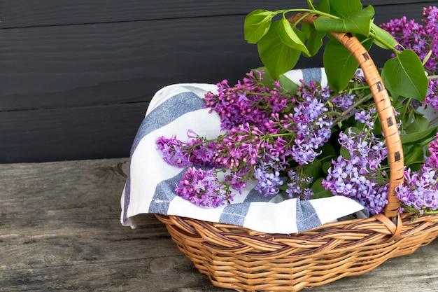 Плетеная корзина с сиренью на деревянный стол. бесплатная копия пространства.