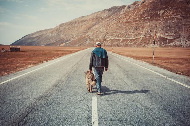 山の中の彼の犬と一緒に道を歩いて男