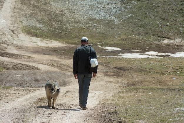 山で彼の犬を連れて歩いて男