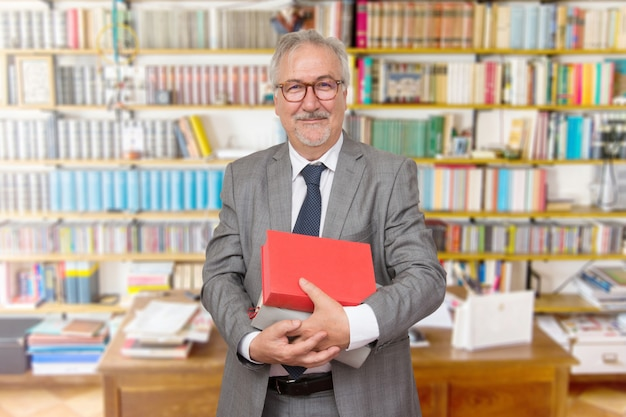 Старший учитель стоял с книгой перед книжным шкафом