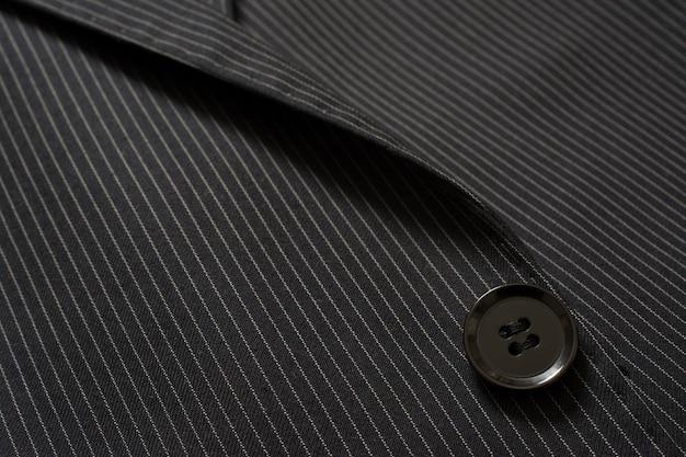 ピンストリップ布のスーツボタンのクローズアップの詳細