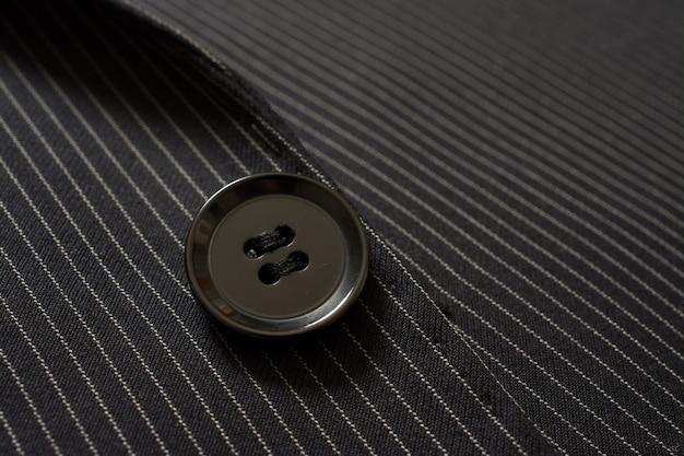 ピンストリップのスーツボタンのクローズアップの詳細。