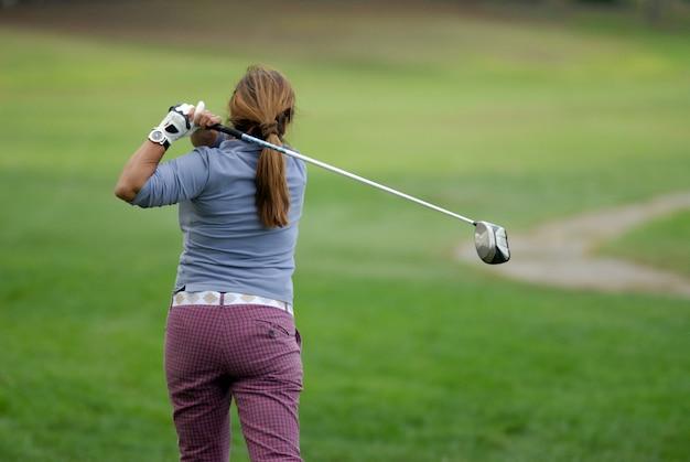 ゴルファーがゴルフボールを撃つ