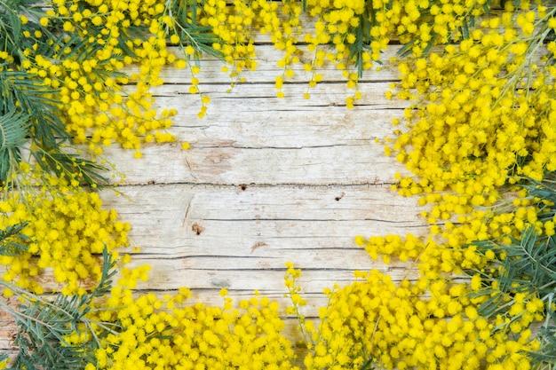 木製の背景にミモザの花のフレーム。