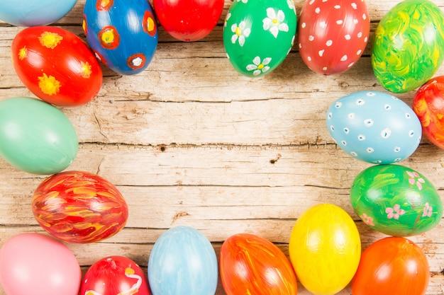 木製のテーブルに手作りの着色された卵をイースターの背景。フレームとコピースペース。