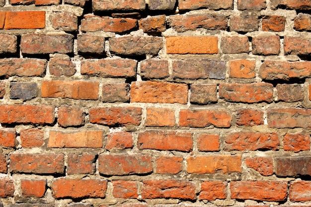 オレンジ色のレンガの古いヴィンテージの壁。建築の抽象的な背景