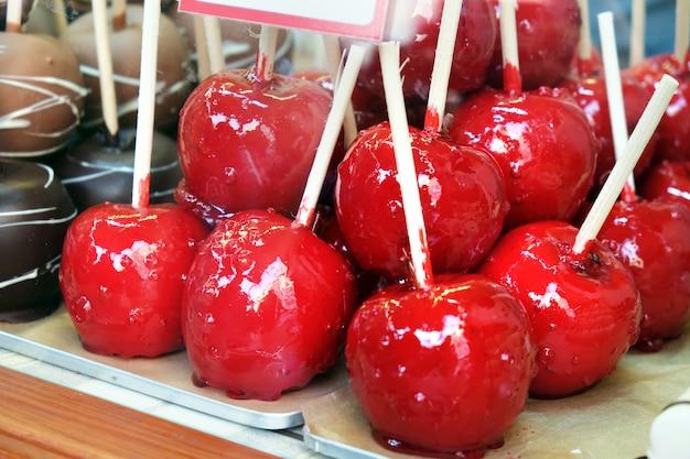 飴屋の窓に赤い釉薬を塗ったリンゴ。艶をかけられたカラメルフルーツ、休日の子供のための御馳走。