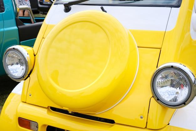 Макрофотография передних фонарей в стиле ретро редкий желтый малолитражный автомобиль фольксваген