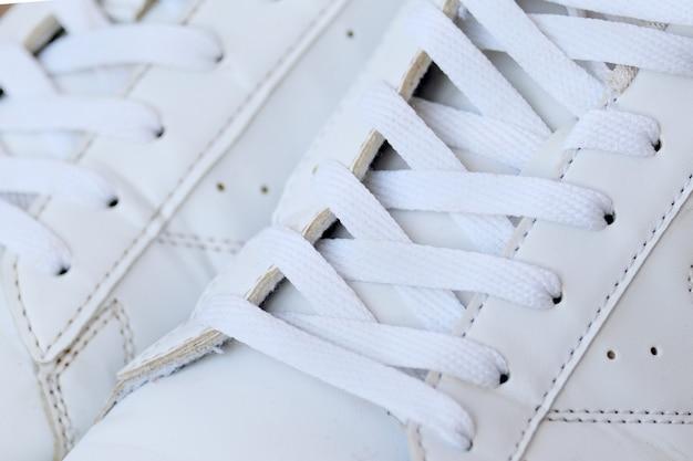 靴ひもが付いた白い中古スニーカーのペア。