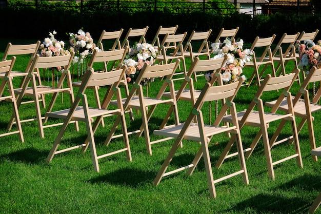 Белые деревянные пустые стулья в ряд и букеты цветков на зеленой траве.