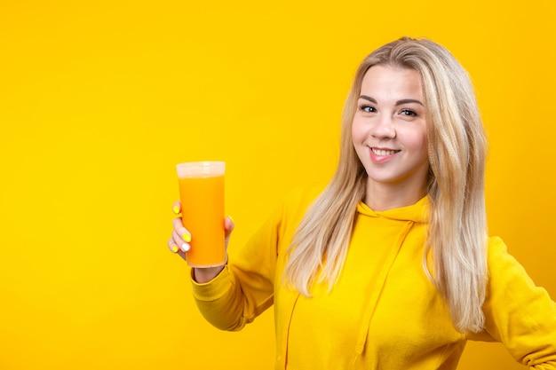 オレンジジュースのガラスを保持している黄色のカジュアルなスポーティな服で幸せな美しい若いブロンドの女性
