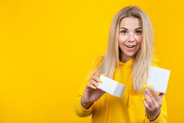Портрет молодой сумасшедшей кавказской блондинкой в желтом спортивном костюме, открыв белую подарочную коробку, изолированный,