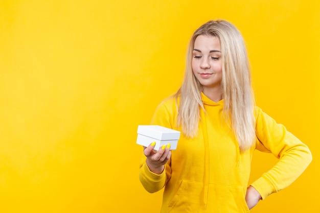 Портрет молодой красивой кавказской белокурой женщины в желтом спортивном костюме, держащей белую подарочную коробку,