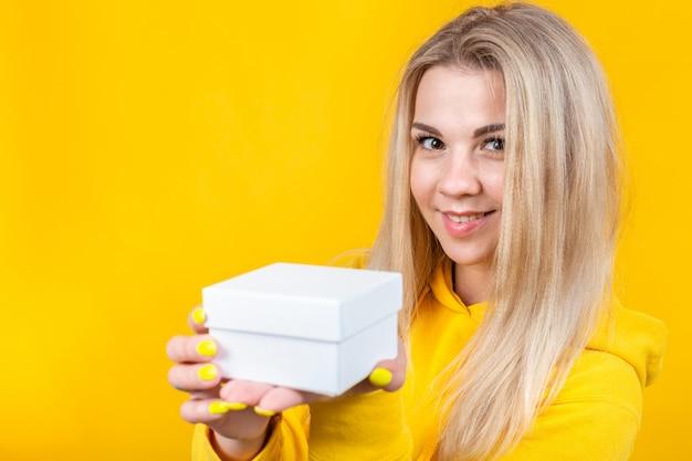 黄色のスポーツスーツの若い魅力的な白人ブロンドの女性の肖像画は、カメラに白いギフトボックスを与える