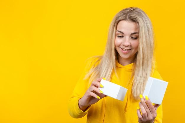 Портрет молодой довольно кавказской белокурой женщины в желтом спортивном костюме, раскрывая белую подарочную коробку, изолированный,