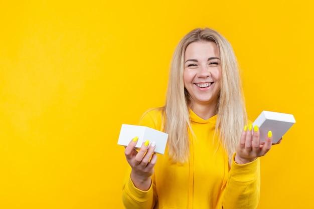 Портрет молодой радостной кавказской белокурой женщины в желтом спортивном костюме, раскрывает белую изолированную подарочную коробку ,.