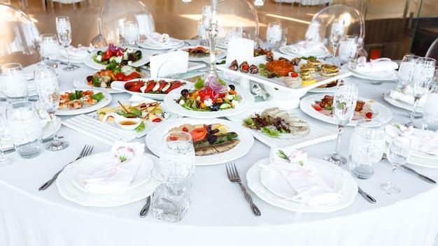 Элегантно украшенный стол с едой и посудой на свадебный прием крупным планом