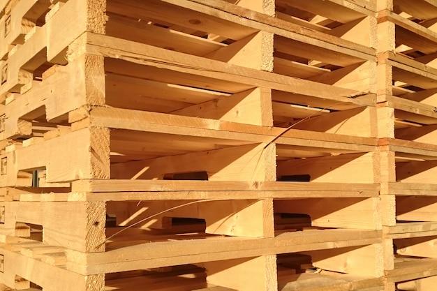 新しい木パレットは貨物配達企業の倉庫に積み重ねられています。