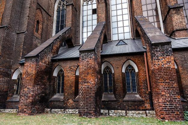 古いカトリック大聖堂の暗いレンガの壁。低キーの背景。