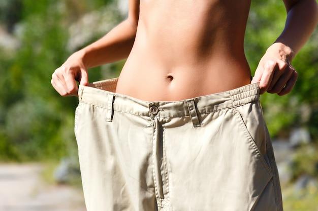 彼女がどれだけの体重を失ったかを示す女性。健康的なライフスタイルのコンセプト