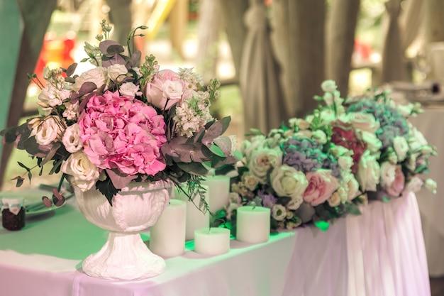 Букеты из роз и эустомы и свечи на украшенном свадебном столе в растуранте.