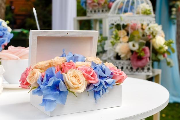 結婚式の屋外のレストランのテーブルでバラの花束を装飾します。