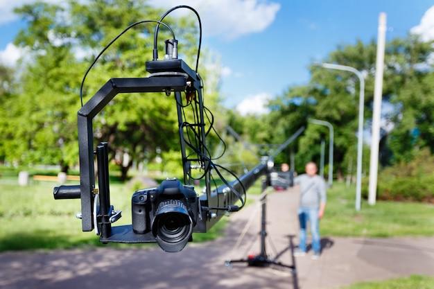 プラットフォームのクローズアップとぼやけているビデオグラファーのフォトカメラ、夏の日に公園でカメラクレーンを使用します。
