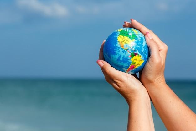 海の背景に地球の世界を保持している女性。