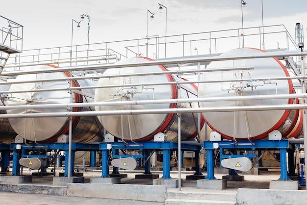 Современное технологическое производственное оборудование винного завода. большие стальные винные перегонные баки.