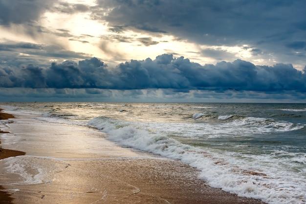 朝の海景に劇的な空。砂浜の海のビーチの日の出。