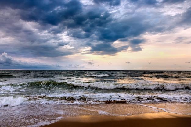 朝の海景に劇的な空。砂浜のビーチで嵐。