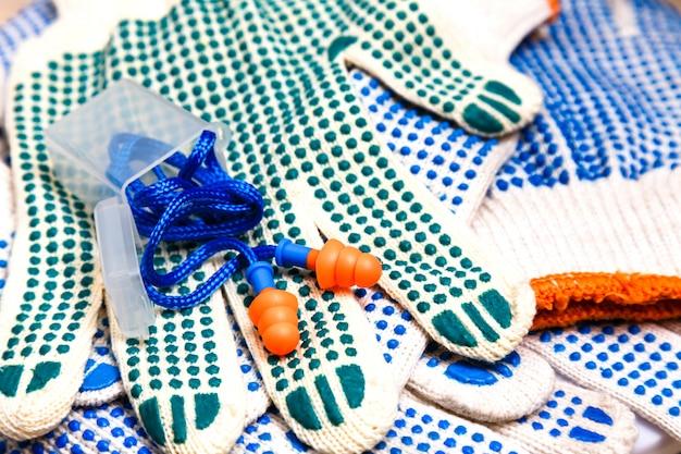 Тонкие рабочие перчатки с зелеными пупырышками и ушными пробками крупным планом