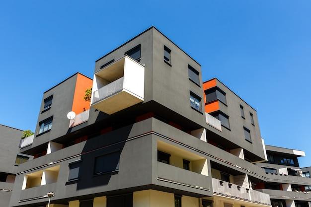 Экстерьер современного многоквартирного дома на голубом небе