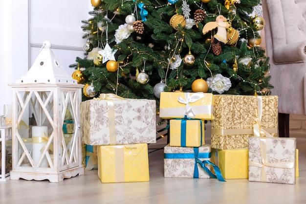 木の近くのクリスマスプレゼントを持つ多くのボックス