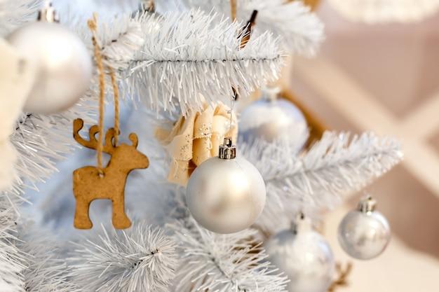 ホワイトクリスマスデコレーションボールは装飾的なホワイトクリスマスツリーに掛かっています。コンセプト新年のお祝いの背景。