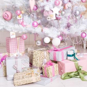 ギフトボックス、装飾的なホワイトクリスマスツリーに掛かっているピンクとホワイトのクリスマスデコレーションボール。コンセプト新年のお祝いの背景。